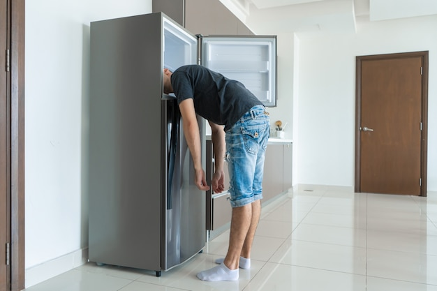 An einem heißen tag kühlt sich der typ mit dem kopf im kühlschrank ab Premium Fotos