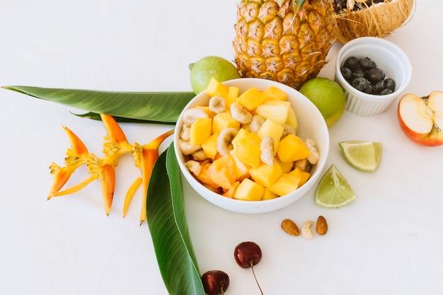 Ananas; bananen- und apfelsalat in der weißen schüssel mit zitronen Kostenlose Fotos