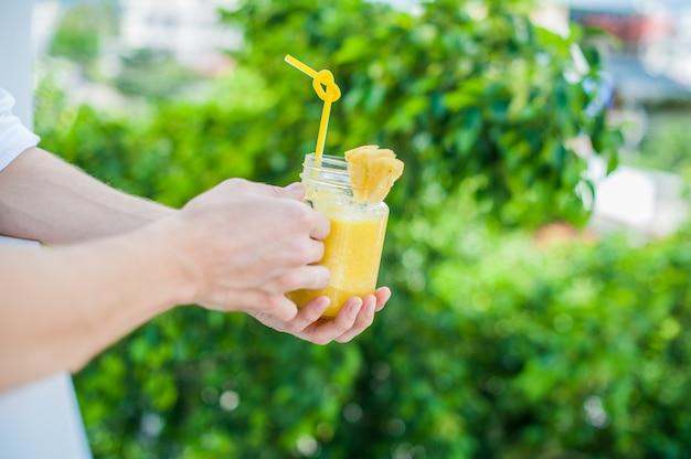 Ananas-cocktail mit einer scheibe in den händen mann auf der terrasse. tropisches konzept Premium Fotos