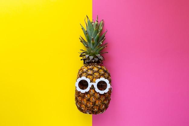 Ananas in der weißen sonnenbrille auf dem bunten hintergrund, kreatives sommerkonzept Premium Fotos