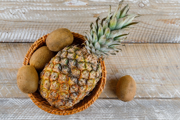 Ananas in einem weidenkorb mit kiwis auf einer holzoberfläche Kostenlose Fotos