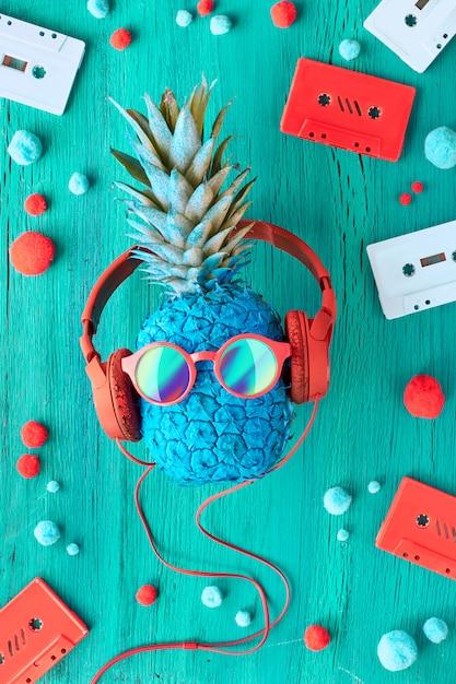 Ananas in sonnenbrille und kopfhörer auf türkisfarbenem holz mit tonbändern Premium Fotos