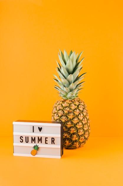 Ananas nahe dem leuchtkasten mit liebessommer des wortes i gegen gelben hintergrund Kostenlose Fotos