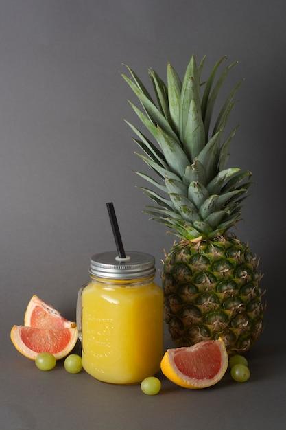 Ananas oder fruchtsaft gläser mit früchten - ananas, orangen, grapefruit, limette und trauben. Premium Fotos
