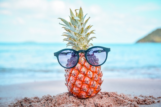 Ananas und sonnenbrillen am strand st. meer sommer Premium Fotos