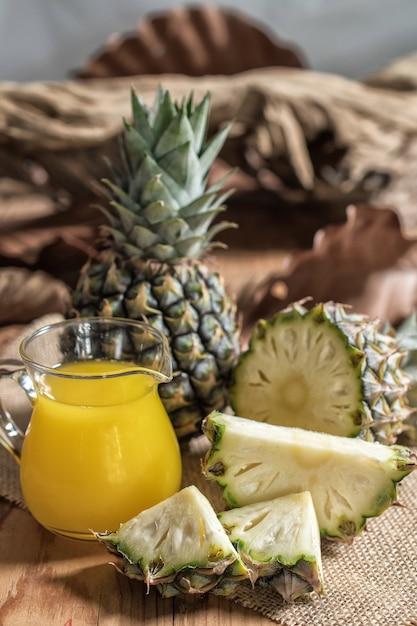 Ananassaft- und -ananasscheibe gesetzt auf einen holztisch. Premium Fotos