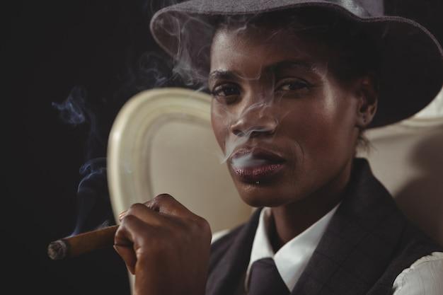 Androgyner mann, der zigarre raucht, während er auf einem stuhl sitzt Premium Fotos