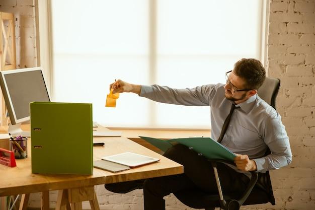 Angebote. ein junger geschäftsmann, der im büro arbeitet und einen neuen arbeitsplatz bekommt. junger männlicher büroangestellter beim verwalten nach der beförderung. sieht ernst und selbstbewusst aus. geschäft, lebensstil, neues lebenskonzept. Kostenlose Fotos