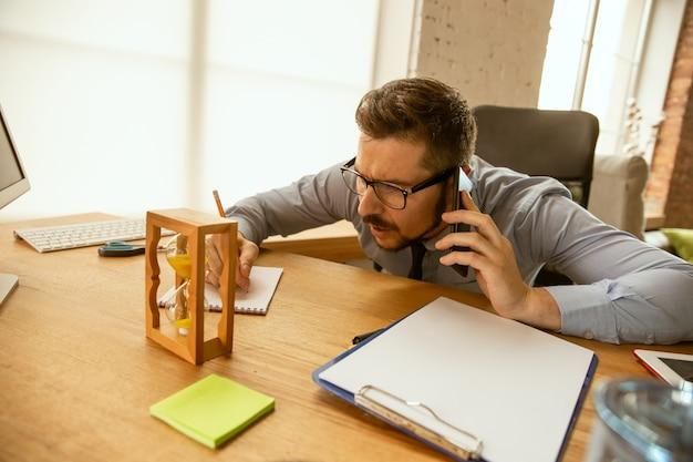Angebote. ein junger geschäftsmann, der im büro arbeitet und einen neuen arbeitsplatz bekommt. junger männlicher büroangestellter beim verwalten nach der beförderung Kostenlose Fotos