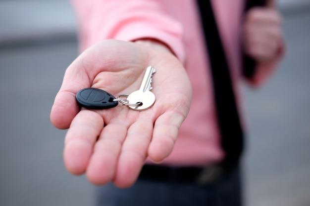 Angebotschlüssel des manngrundstücksmaklers von der handnahaufnahme des neuen hauses Premium Fotos