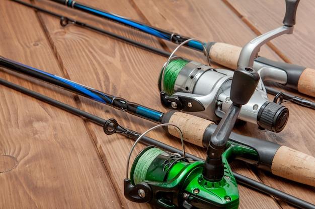 Angelausrüstung - fischen, spinnen, haken und köder auf hölzernem hintergrund mit kopienraum Premium Fotos