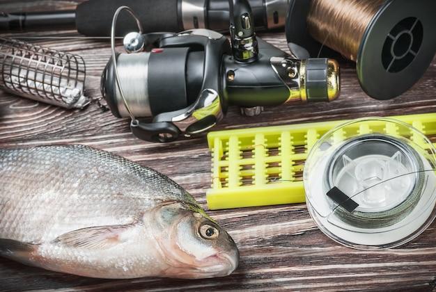 Angelausrüstung und gefischter brachsen auf einem holztisch Premium Fotos