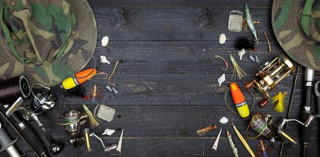 Angelruten und rollen, angelausrüstung auf schwarzem hintergrund aus holz Premium Fotos