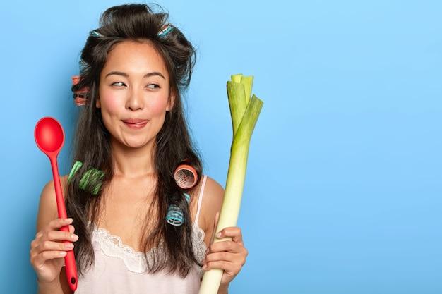 Angenehm aussehende brünette hausfrau mit asiatischem aussehen, hält löffel und grünen lauch, bereitet vegetarisches frühstück zu Kostenlose Fotos