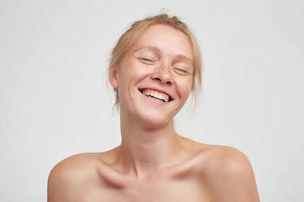 Angenehm aussehende junge rothaarige frau mit lässiger frisur, die ihre augen geschlossen hält, während sie glücklich lächelt, ihre augen geschlossen hält, während sie über weißem hintergrund steht Kostenlose Fotos