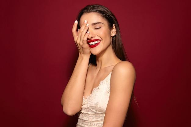 Angenehm aussehende junge ziemlich froh langhaarige brünette dame mit roten lippen Kostenlose Fotos