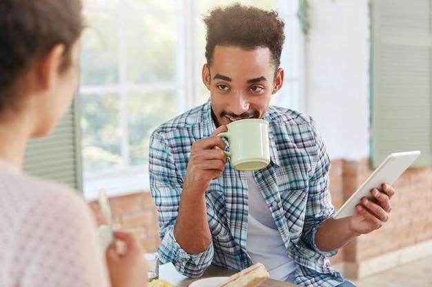 Angenehm aussehender mann mit spezifischem aussehen trinkt kaffee mit kuchen, spricht mit seiner frau, Kostenlose Fotos