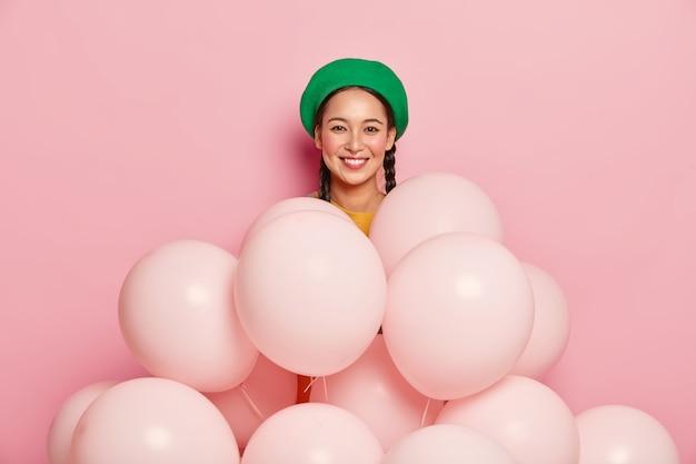Angenehm aussehendes asiatisches weibliches modell trägt grüne baskenmütze, steht in der nähe vieler luftballons, posiert über rosa hintergrund, feiert geburtstag Kostenlose Fotos