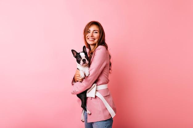 Angenehme kaukasische frau in der rosa kleidung, die welpen umarmt. glamouröses weißes mädchen, das französische bulldogge mit lächeln hält. Kostenlose Fotos