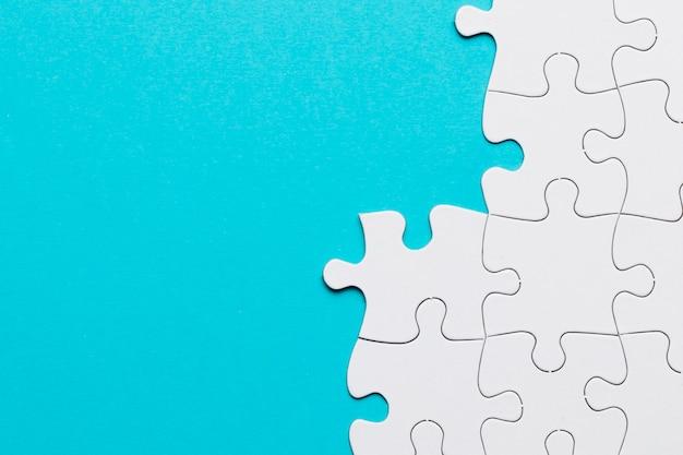 Angeordnetes weißes puzzlespiel auf blauer oberfläche Kostenlose Fotos