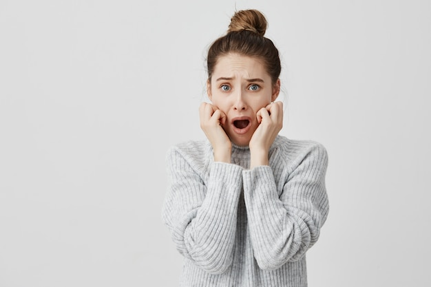 Angst frau in grauem pullover hält ihre hand auf den wangen mit geöffnetem mund erschrocken. grafikdesignerin, die sich sorgen um fehlende frist macht. verstoßkonzept Kostenlose Fotos