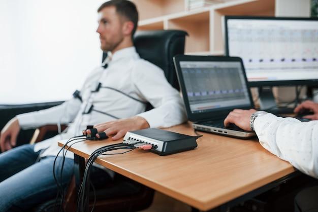 Angst zeigt, dass sie nicht so ehrlich sind. verdächtiger mann übergibt lügendetektor im büro. fragen stellen. polygraphentest Kostenlose Fotos