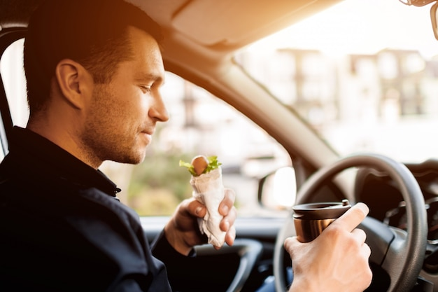 Anhalten, um etwas zu essen. mann essen snack im auto und