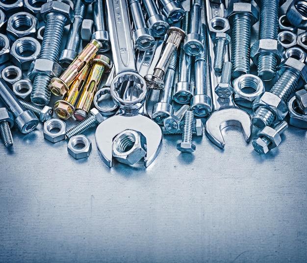 Ankerbolzen bolzendetails muttern hakenschlüssel und flacher schraubenschlüssel auf metallischem hintergrundkonstruktionskonzept Premium Fotos