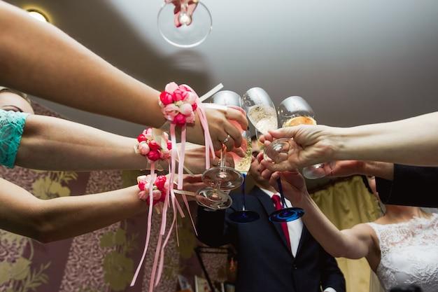 Anklopfen der gläser bei der hochzeit. hochzeitsgäste trinken champagner Premium Fotos