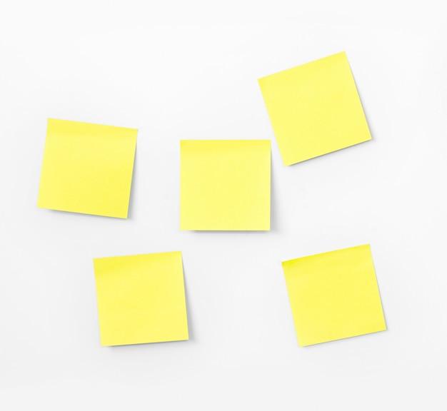 Anmerkungspapier auf weißer wand Premium Fotos