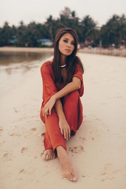 Anmutige frau, die am strand aufwirft, sitzt auf sand im roten kleid Kostenlose Fotos