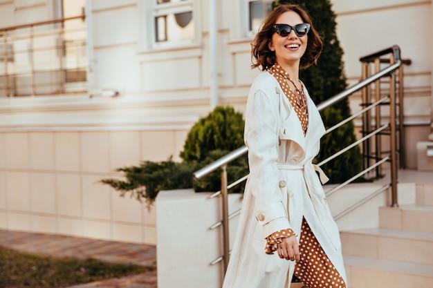 Anmutige frau im weißen kittel und in der sonnenbrille, die glückliche gefühle ausdrückt. außenaufnahme der schönen dame im eleganten herbstoutfit. Kostenlose Fotos