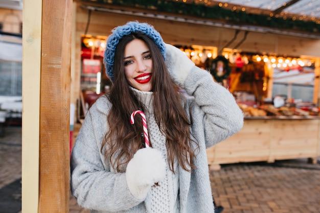 Anmutige schwarzhaarige frau mit zuckerstangenlächeln. außenporträt des atemberaubenden modischen mädchens in den weißen handschuhen, die spaß auf weihnachtsmarkt haben. Kostenlose Fotos