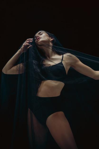Anmutiger klassischer balletttänzer, der lokalisiert auf schwarzem studiohintergrund tanzt. Kostenlose Fotos
