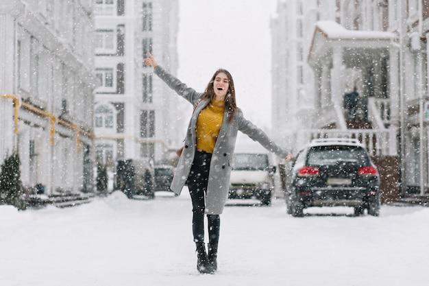 Anmutiges kaukasisches weibliches modell im langen mantel, der auf der straße im wintermorgen tanzt. außenfoto der bezaubernden dame im gelben pullover, der hände während des fotoshootings am frostigen tag winkt. Kostenlose Fotos