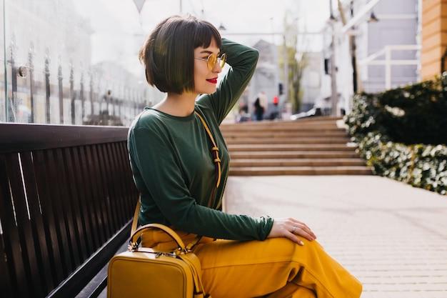 Anmutiges kurzhaariges mädchen in der sonnenbrille, die draußen entspannt. entzückende frau im grünen pullover, der auf bank in sonnigem tag aufwirft. Kostenlose Fotos