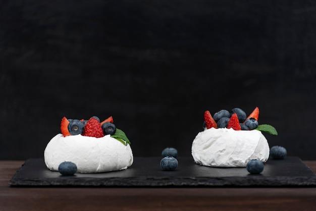 Anna pavlova kuchen auf schwarzem hintergrund. luft baiserkuchen mit frischen erdbeeren und blaubeeren. Premium Fotos