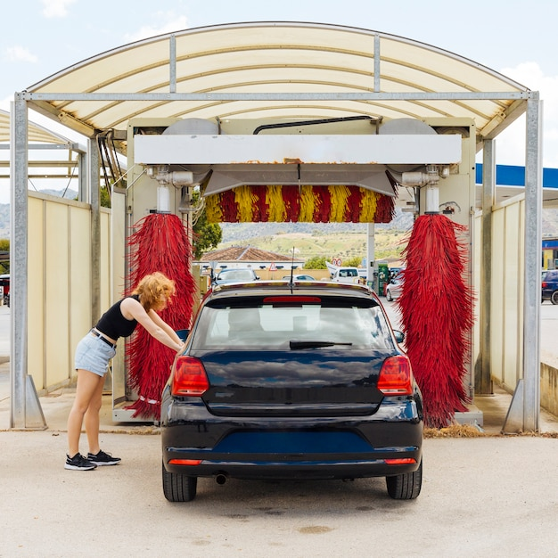 Anonyme frau, die auf auto vor autowäsche sich lehnt Kostenlose Fotos