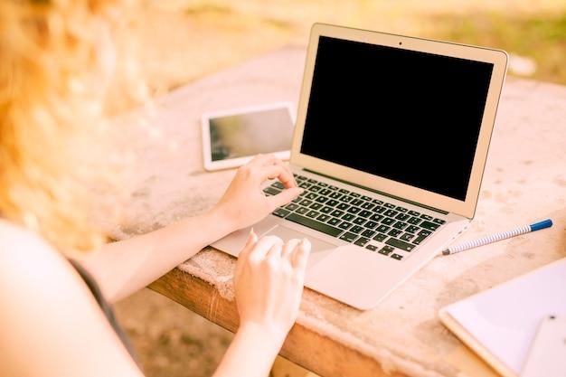 Anonyme frau, die draußen an laptop am schreibtisch arbeitet Kostenlose Fotos