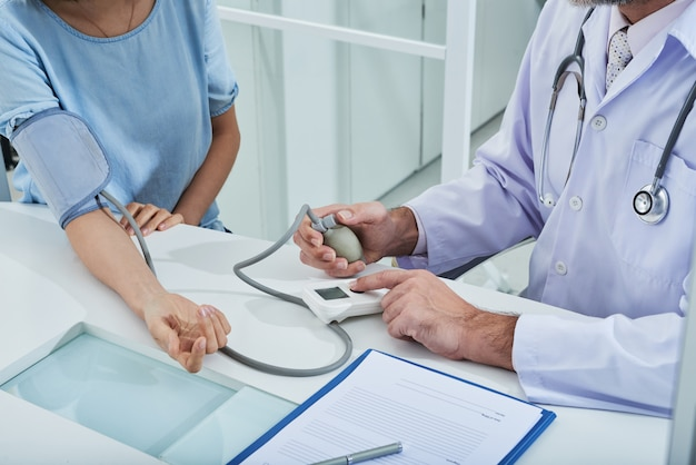 Anonymer arzt misst den blutdruck an einem nicht wiedererkennbaren patienten mit einem tonometer Kostenlose Fotos