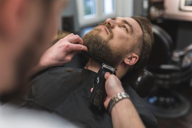 Anonymer barbier, der bart des mannes trimmt Kostenlose Fotos
