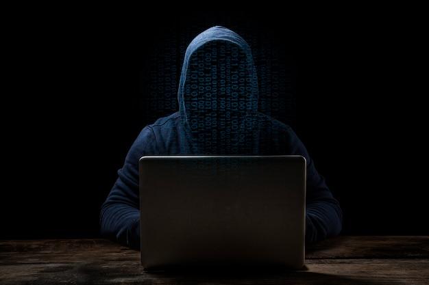 Anonymer computerhacker über abstraktem digitalem hintergrund. verdecktes dunkles gesicht in maske und kapuze. Premium Fotos