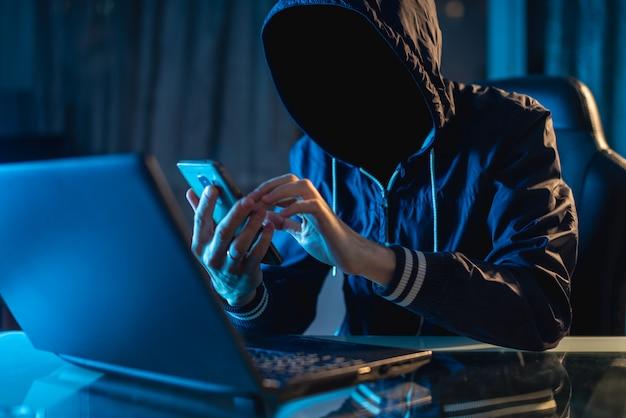 Anonymer hacker-programmierer benutzt einen laptop, um das system im dunkeln zu hacken. konzept der internetkriminalität und hacking-datenbank Premium Fotos