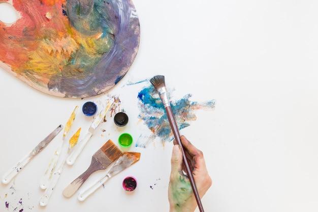 Anonymer maler, der malerpinsel und farbton verwendet Kostenlose Fotos