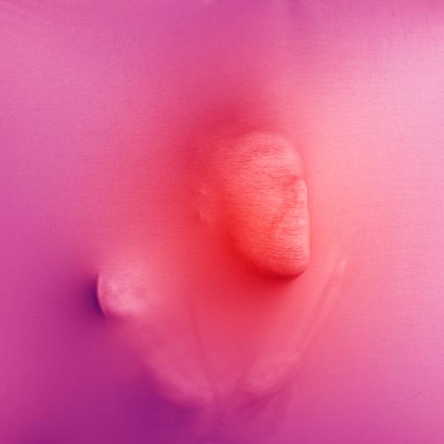 Anonymer mann, der rosafarbenen stoff drückt Kostenlose Fotos