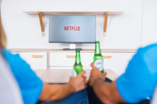 Anonymes paar mit bier, das fernsehshows genießt Kostenlose Fotos