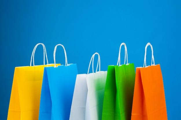Anordnung der einkaufstaschen auf blauem hintergrund Premium Fotos