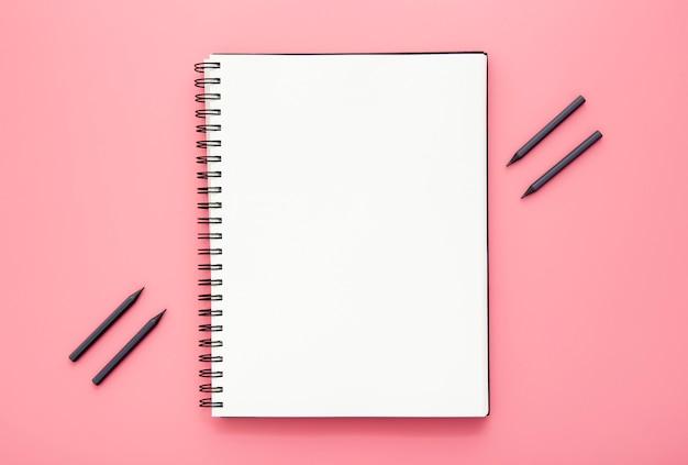 Anordnung der schreibtischelemente mit leerem notizblock auf rosa hintergrund Premium Fotos
