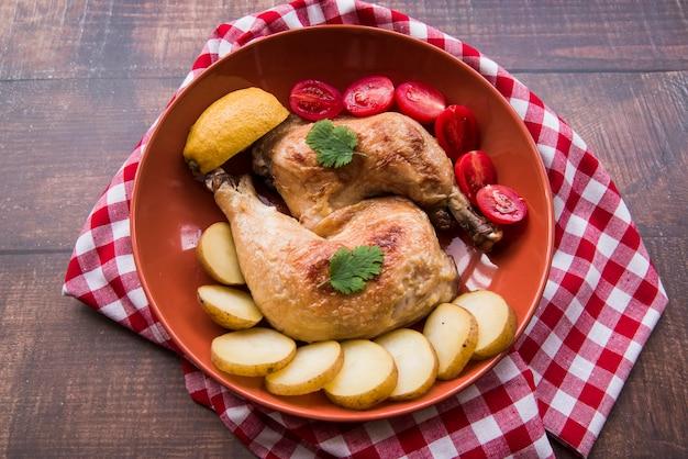 Anordnung für gegrillte hühnerbeine mit tomaten- und kartoffelscheiben in der schüssel über tischdecke Kostenlose Fotos