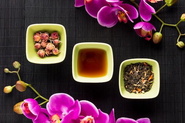 Anordnung für kräutertee und rosa orchideenblume über schwarzer platzmatte Kostenlose Fotos